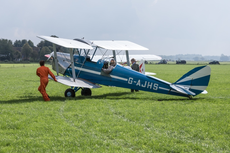 Historical airplane with pilot and mechanics.