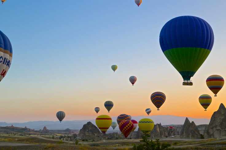 Many hot air balloons in the sky.  An early morning flight in a beautifully coloured balloon.